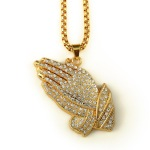 A thick gold chain with a large gold pendant of praying hands fully encrusted with diamonds.