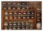 A wooden lazy susan spice rack with two shelves. On each shelf are clear glass jars containing various herbs and spices. Photo courtesy of https://shut10dvi.wordpress.com/2015/06/19/how-to-build-lazy-susan-spice-rack-plans-plans-woodworking-wooden-dvd-rack/