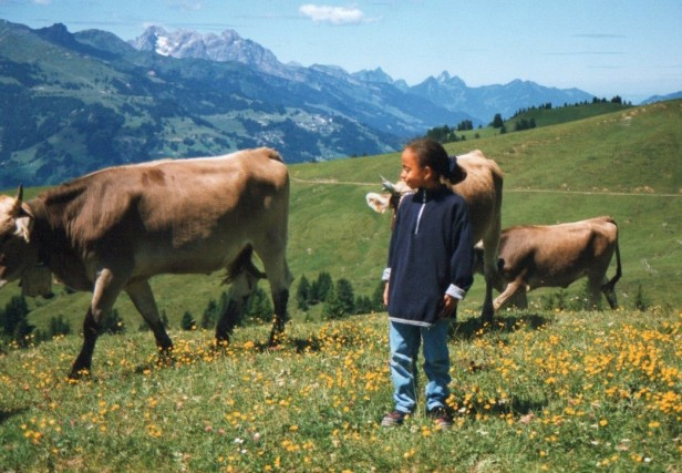 Eight-year old Keshia at Buchberg, Schaffhausen dressed in light blue jeans and a dark blue sweater with three brown cows behind her.
