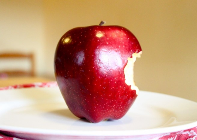 On top of a red and white tablecloth sits a white plate with a shiny red apple. The apple has a jagged bite taken out of the right side. Image courtesy of www.inabeautifulmess.com