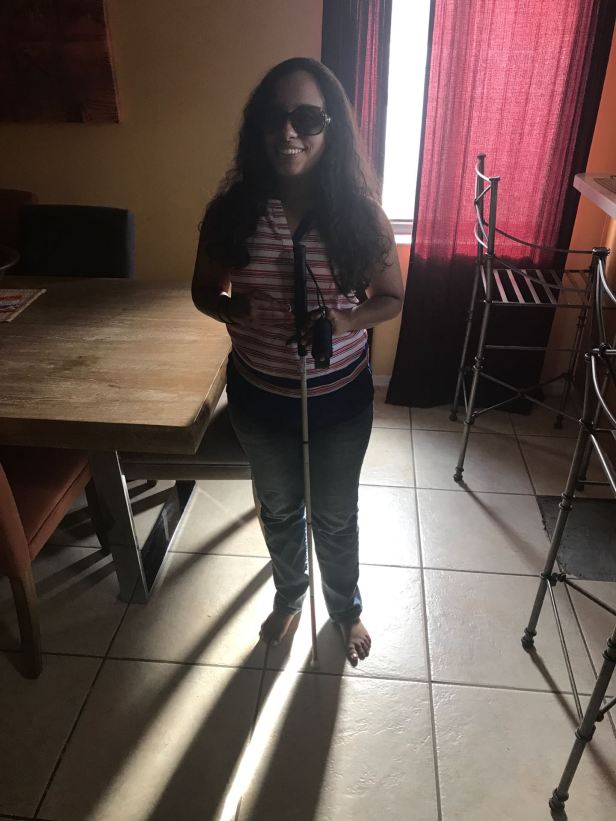 Keshia smiling broadly, her long dark hair framing her face in fashionable sunglasses. Wearing a red and white sleevless top and blue jeans, holding a Revolution mobility cane with a pepper spray holder tied to the handle loop of her cane. Standing in front of a brightly lit window with red curtains.