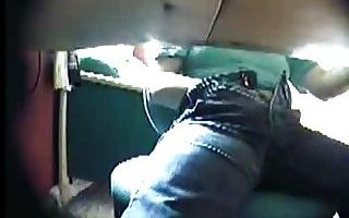 From under a desk we see a white male wearing a green shirt and blue jeans with his right-hand inside his pants on his crotch.