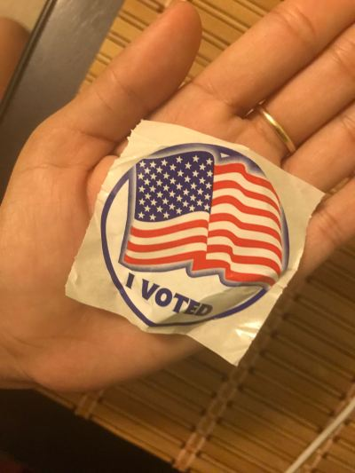 "In the author's openpalm is a circular, unused sticker displaying the image of a red, white, and blue cartoon American flag and the words ""I Voted"" in blue, block lettering below on a white background."