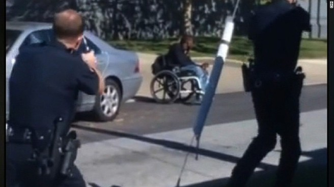 We see the backs of two white male cops pointing guns at a black man in a wheelchair. They are all in the street.
