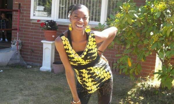 Pictured from the knees up, Charleena Lyles can be sseen standing in front of a house wearing a bright black and yellow top with matching earrings, smiling at the camera with one hand on her hip. In the far background, we see a small child standing on a stoop. This picture was found at https://www.theguardian.com/us-news/2017/jun/22/police-killings-disabled-black-people-mental-illness