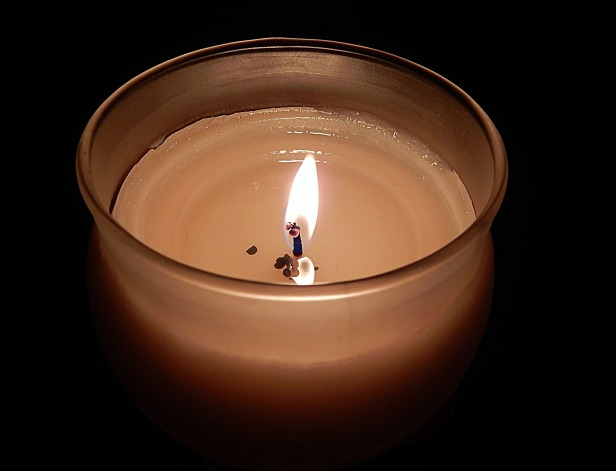 A lit white candle in a glass jar sits in a dark room.