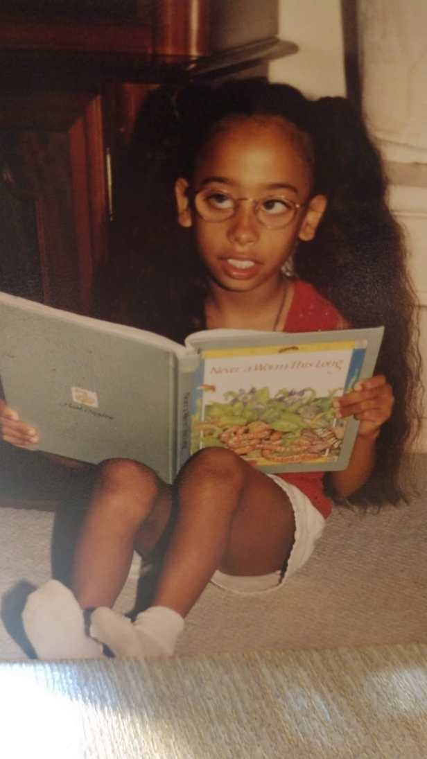 Keshia, age 7, sits on the floor with a book propped up on her knees. She has thick glasses on, her waist-length hair is done in pigtails, and she's wearing a pink shirt, white shorts and white socks. She stares to the left of the camera with a hard-to-read expression.