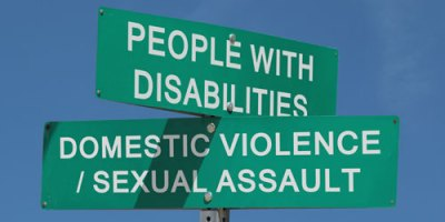"Green Street Sign depicting the intersection of ""People With Disabilities"" and ""Domestic Violence/Sexual Assault"""